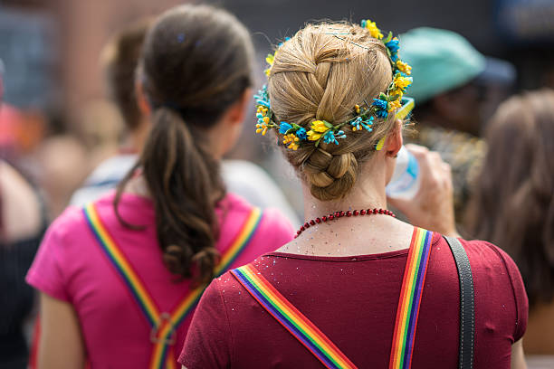 young blonde woman in a crowd celebrating pride parade. - modefarben sommer 2016 stock-fotos und bilder