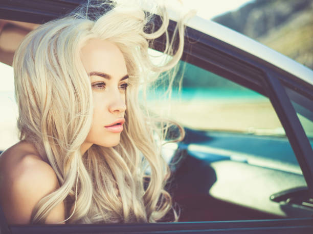 junge blonde frau im auto - soup_studio stock-fotos und bilder