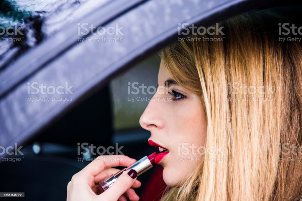 Young blonde woman is correcting her makeup, painting her lips with lipstick in a rear view mirror of her car. zbiór zdjęć royalty-free