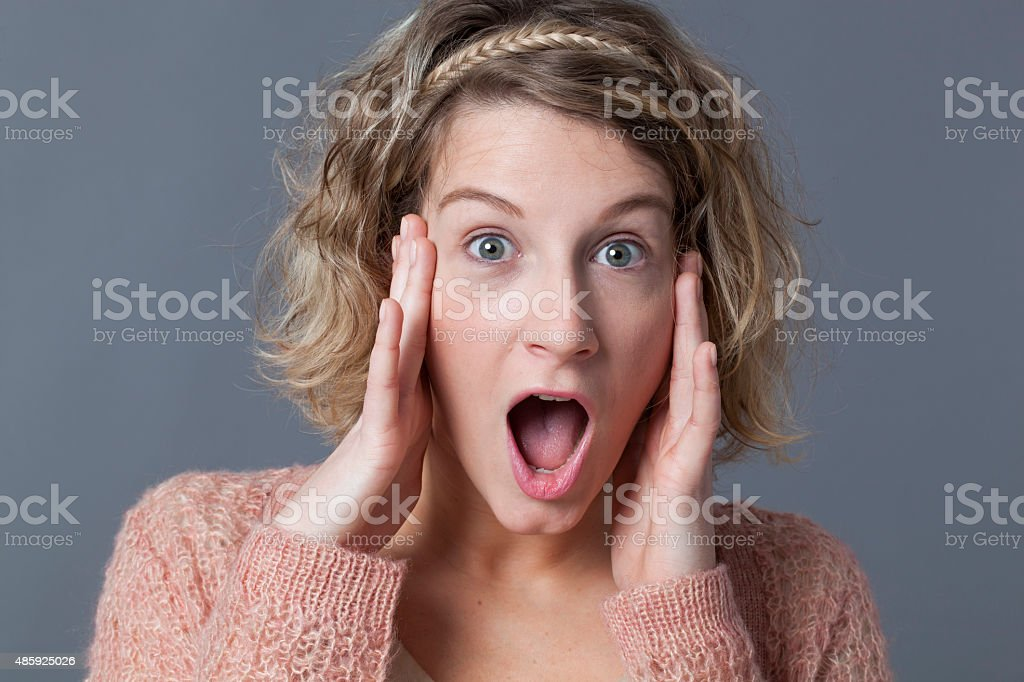 young blonde woman looking surprised stock photo
