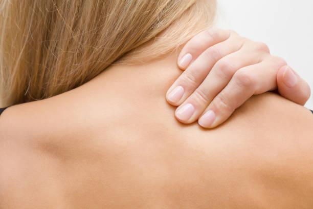 junge, blonde frau massiert ihre nackten schulter mit der hand. schmerzen von belastungen und fehlhaltungen. inaktiven lebensstil. - chiropraktik wellness stock-fotos und bilder