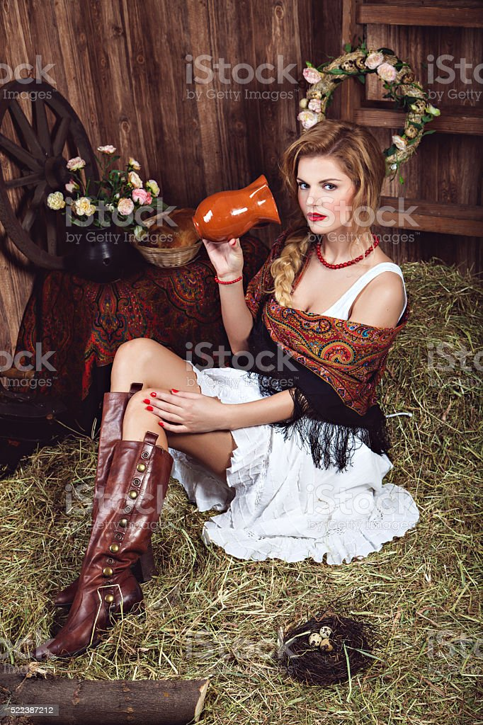 Young blonde woman on the straw in rustic style stock photo