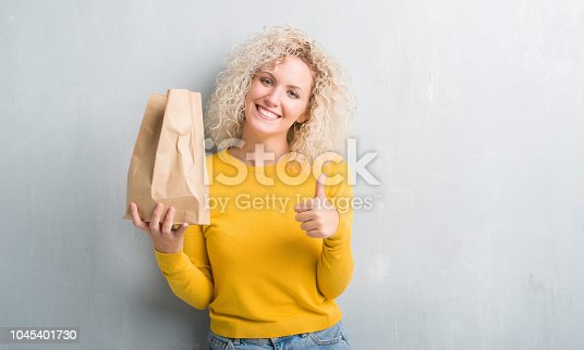 Young blonde woman over grunge grey background holding lunch paper bag happy with big smile doing ok sign, thumb up with fingers, excellent sign