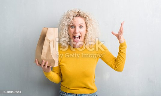 Young blonde woman over grunge grey background holding lunch paper bag very happy and excited, winner expression celebrating victory screaming with big smile and raised hands