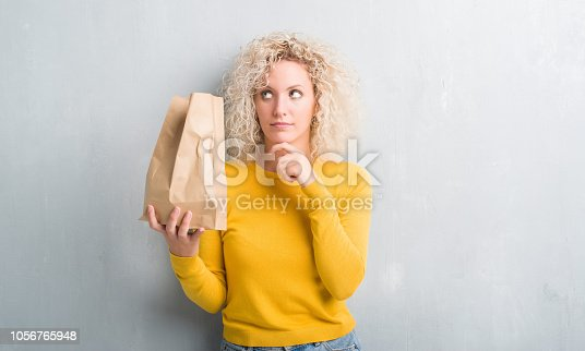 Young blonde woman over grunge grey background holding lunch paper bag serious face thinking about question, very confused idea