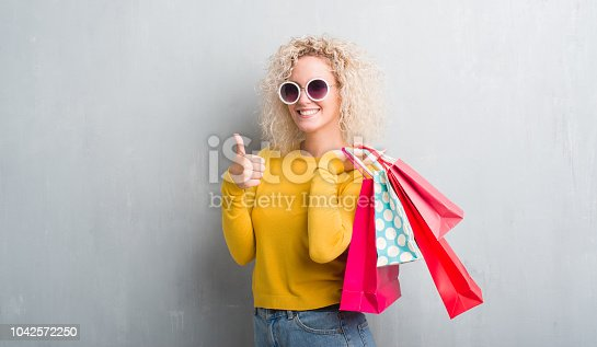 Young blonde woman over grunge grey background holding shopping bags on sales happy with big smile doing ok sign, thumb up with fingers, excellent sign