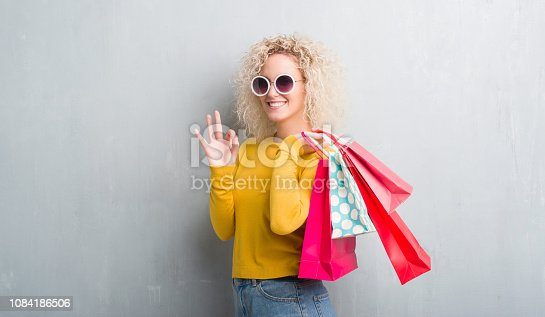 Young blonde woman over grunge grey background holding shopping bags on sales doing ok sign with fingers, excellent symbol