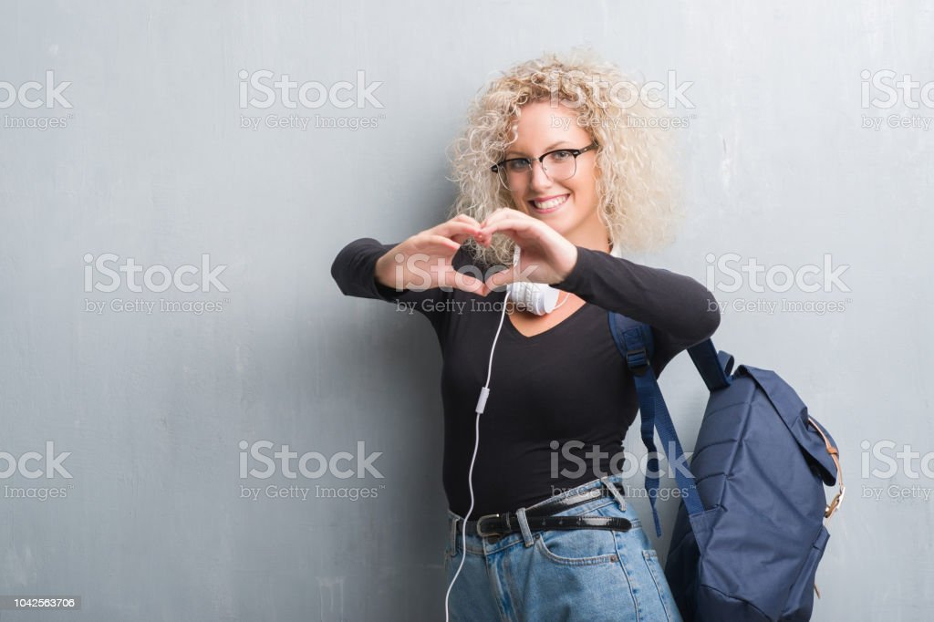 Young blonde woman over grunge grey wall wearing backpack and headphones smiling in love showing heart symbol and shape with hands. Romantic concept. stock photo