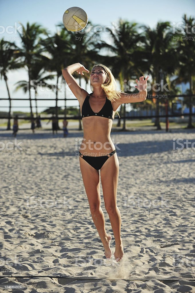 Young Blonde Woman playing beach volleyball, serving stock photo