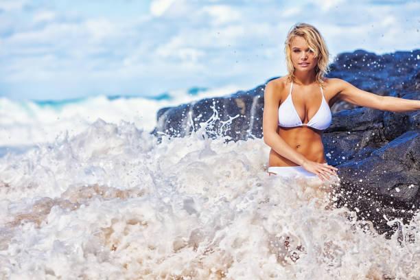 Young Blonde Woman Posing on Hawaiian Beach Among Violent Waves stock photo