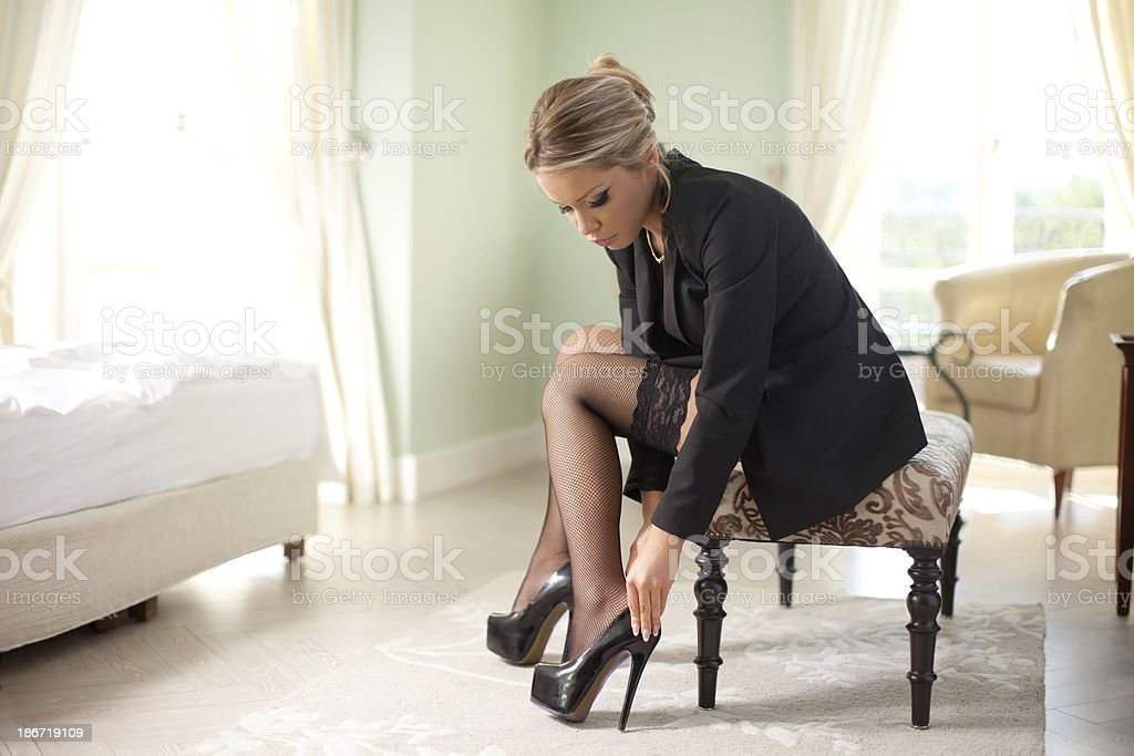 Young blonde woman putting on her shoes royalty-free stock photo