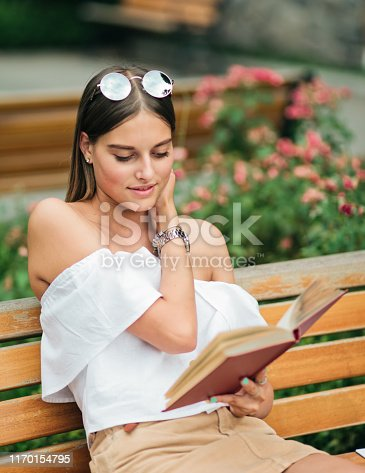 862602714 istock photo Young blonde woman reading a book with enthusiasm while sitting on a bench in park 1170154795