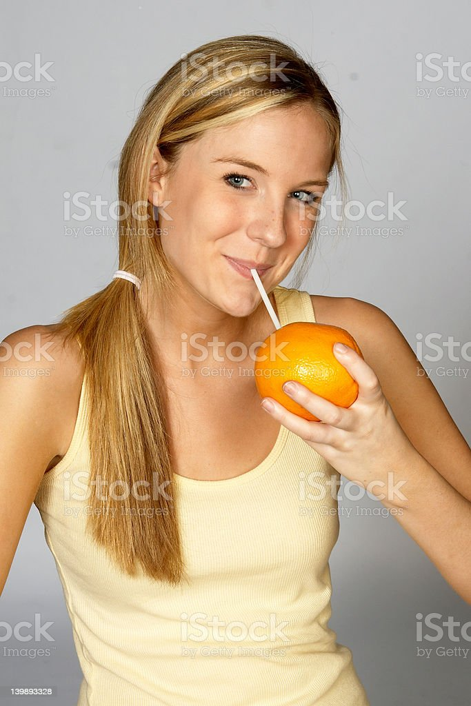 Young Blonde Woman Sipping Juice from Orange royalty-free stock photo
