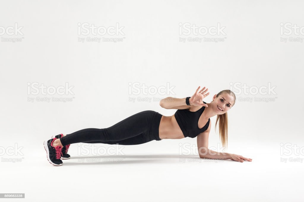 Young blonde woman standing in plank. Studio shot stock photo