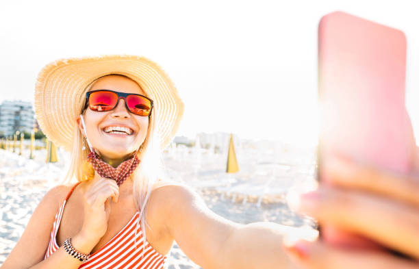 Young blonde woman taking happy selfie with open facial mask and sunglasses - New normal lifestyle concept with millenial girl having fun at beach - Warm bright sunshine filter with focus on face stock photo