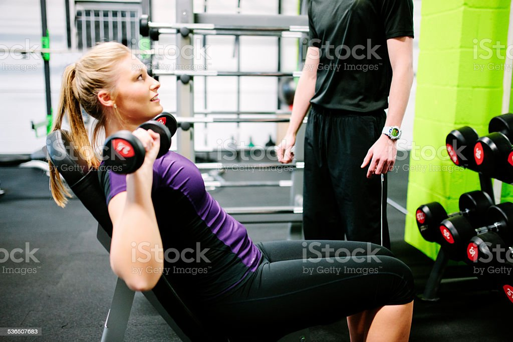 Young, blonde woman using hand weights in a gym stock photo