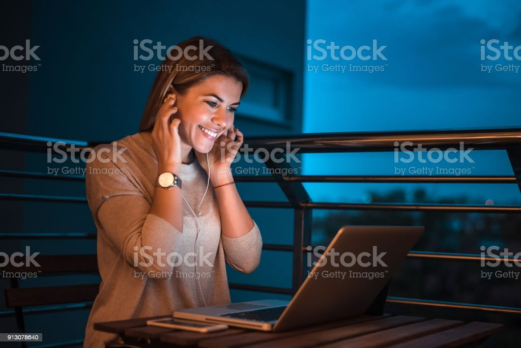Young blonde woman using laptop late and listening to music. High ISO image. stock photo