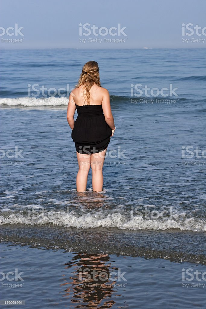 Young Blonde Woman wading in the ocean at evening. royalty-free stock photo
