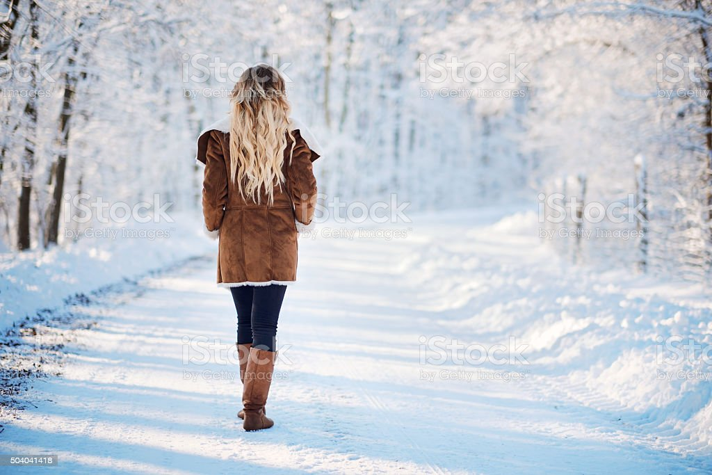 Young blonde woman walking winter park stock photo