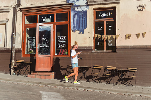 Vilnus / Lithuania - June 9, 2020: young blonde woman walks looking at phone in front of cafeteria in the historic center of the capital