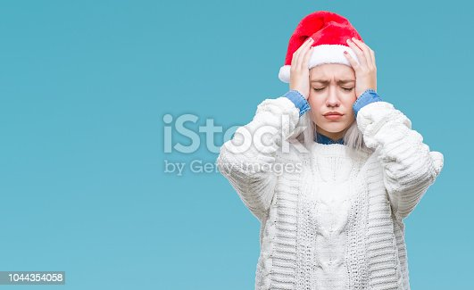 istock Young blonde woman wearing christmas hat over isolated background suffering from headache desperate and stressed because pain and migraine. Hands on head. 1044354058
