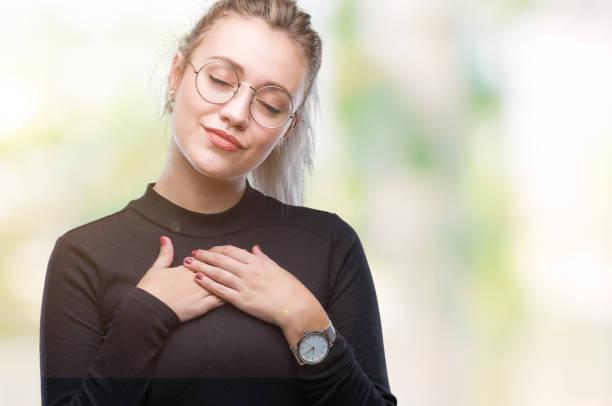 junge blonde frau mit brille über isolierte hintergrund lächelnd mit die hände auf die brust mit geschlossenen augen und dankbar geste auf gesicht. gesundheitskonzept. - die wahrheit tut weh stock-fotos und bilder