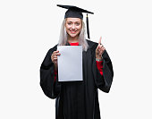 istock Young blonde woman wearing graduate uniform holding degree over isolated background surprised with an idea or question pointing finger with happy face, number one 1071458804