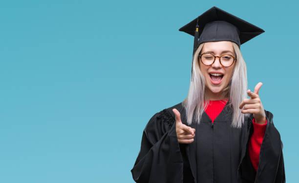 joven mujer rubia vestida con uniforme de postgrado sobre fondo aislado, apuntando los dedos a la cámara con cara de feliz y divertida. buena energía y vibra. - graduación fotografías e imágenes de stock