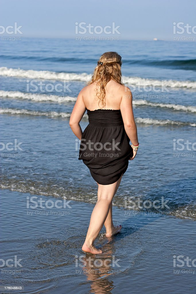 Young Blonde Woman with black dress wading in ocean royalty-free stock photo