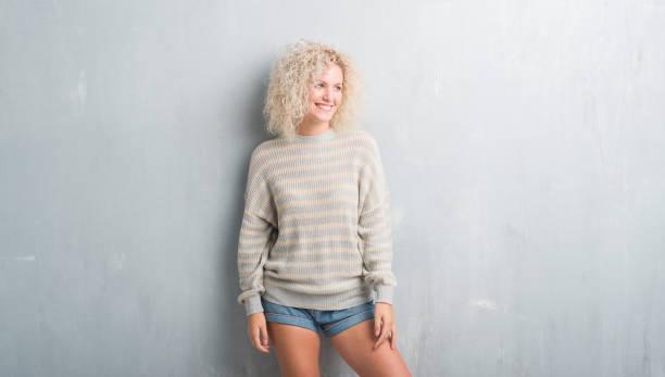 jonge blonde vrouw met krullend haar over grunge grijze achtergrond op zoek weg aan kant met glimlach op het gezicht, natuurlijke wijze van uitdrukking. lachen er alle vertrouwen in. - blond curly hair stockfoto's en -beelden