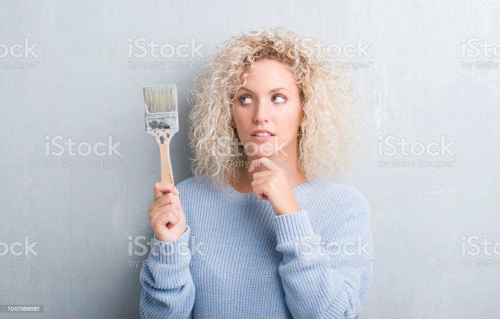 그런 지 회색 배경에 질문, 매우 혼란 스 러 워 아이디어에 대해 페인트 브러시 심각한 얼굴 생각 들고 곱슬 머리를 가진 젊은 금발 여자 스톡 사진