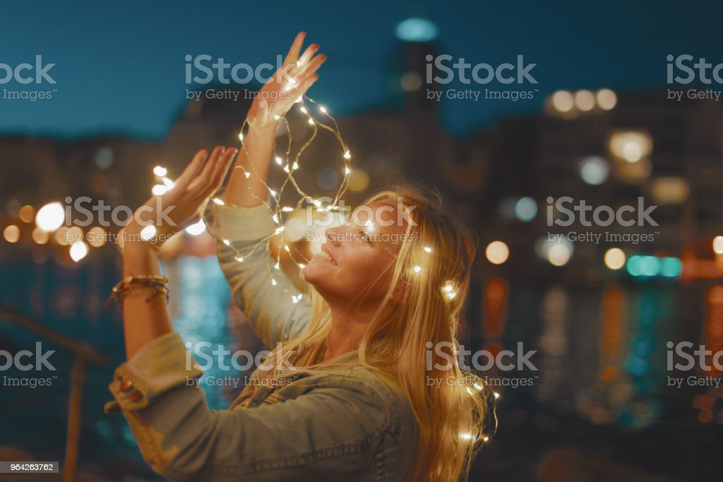 Young blonde woman with garland fairy lights have fun in city at night stock photo
