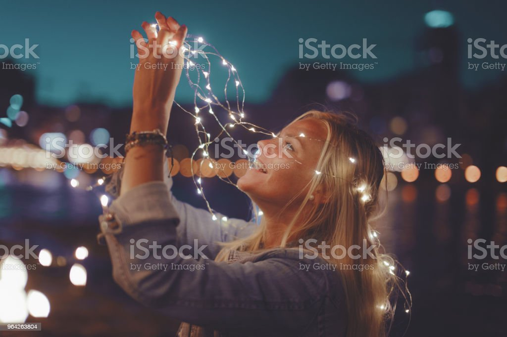 Young blonde woman with garland fairy lights have fun in city at night vintage stock photo