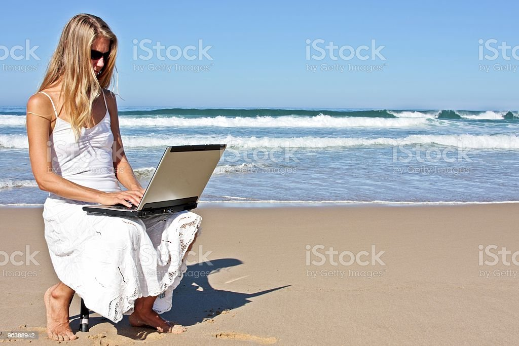 Young blonde woman working on her laptop at the beach - Royalty-free Adult Stock Photo