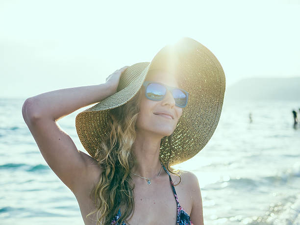 Young blondy girl in sunglasses and straw hat stock photo