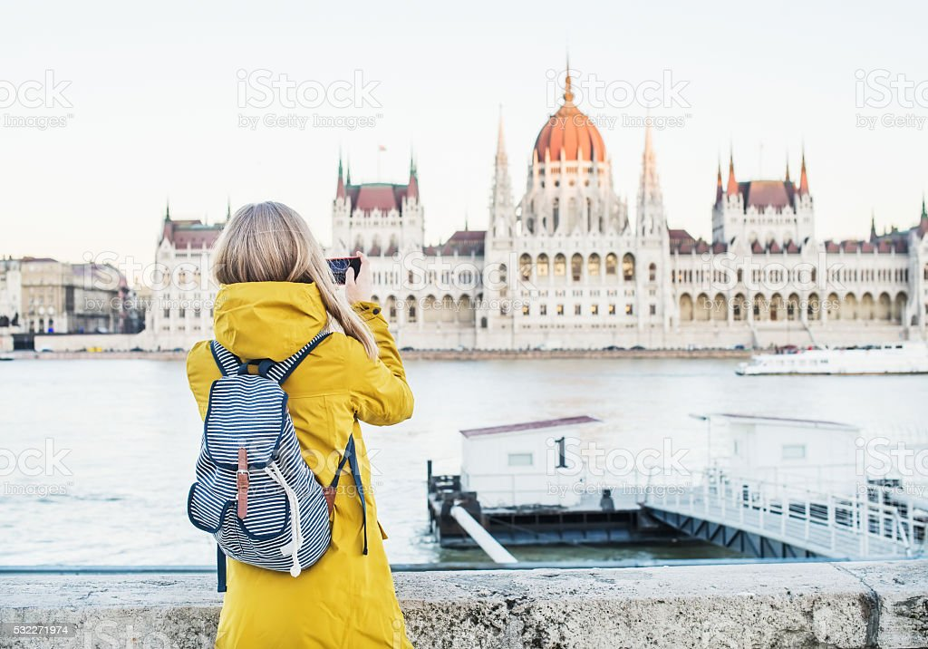 Young blondy woman tourist making photos of Parliament historic building stock photo