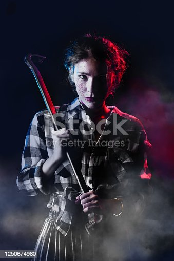 serious young bloody woman with crowbar in dark looking at camera toned image
