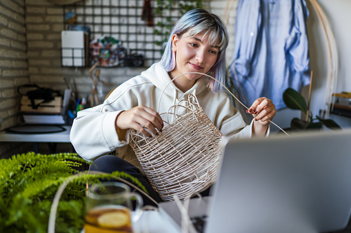 Young Blue haired woman knitting a wicker pot at home using laptop for watching online tutorial