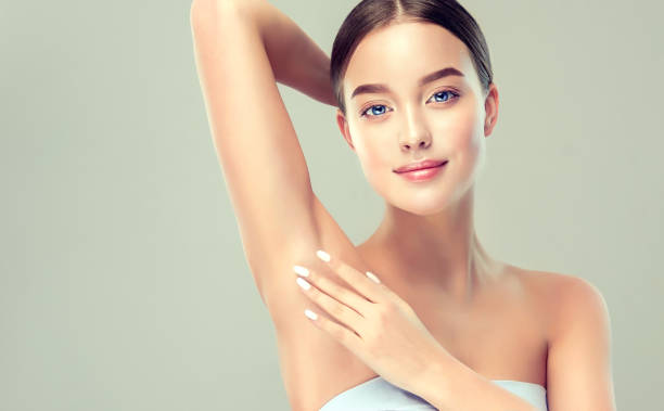 Young, blue-eyed woman is holding her arm up and showing clean underarm. Cosmetology and armpit epilation.  Cosmetology. stock photo