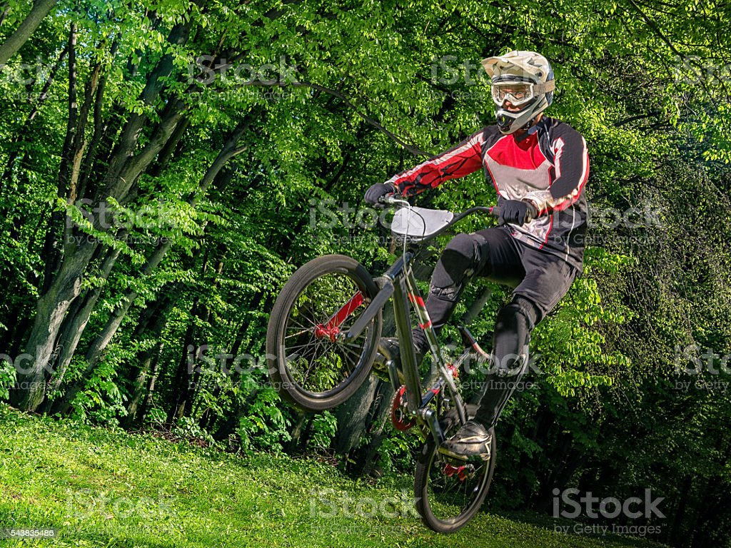 Young bmx bicycle rider on background of trees stock photo