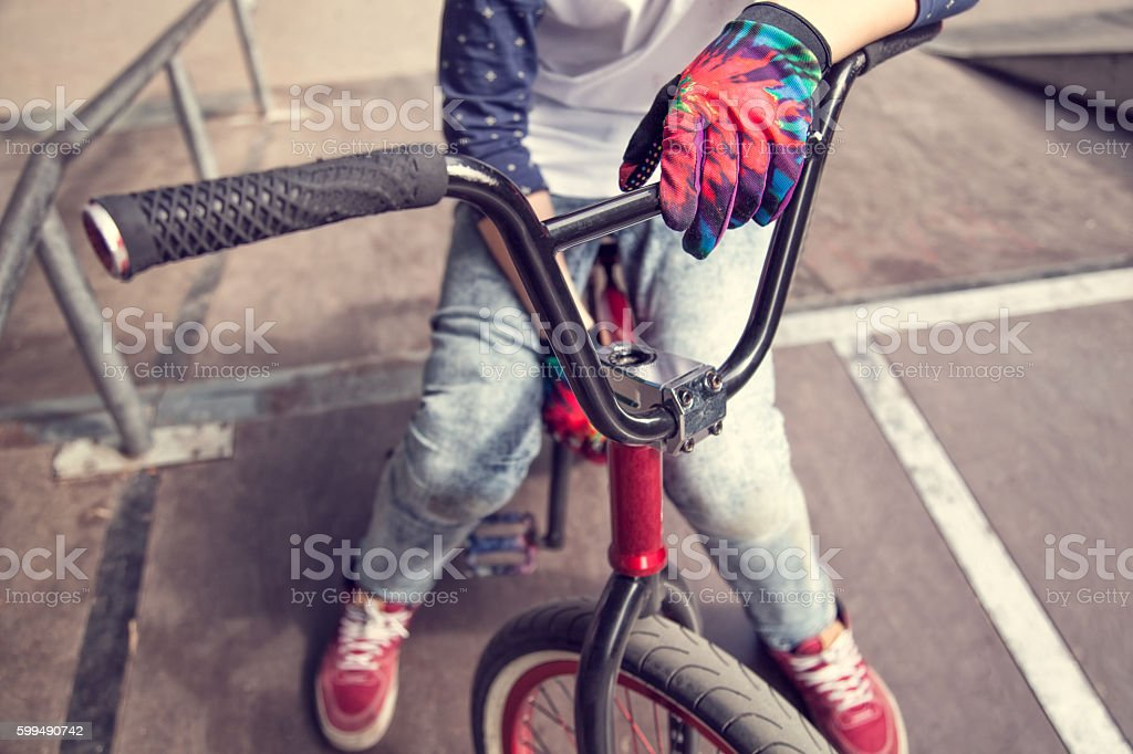 Young BMX rider boy sitting on a bicycle at the top of a ramp in...