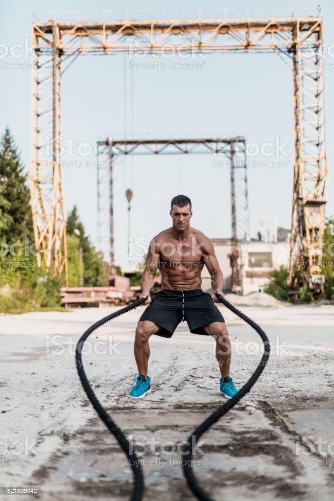 Young bodybuilder exercising with a rope stock photo
