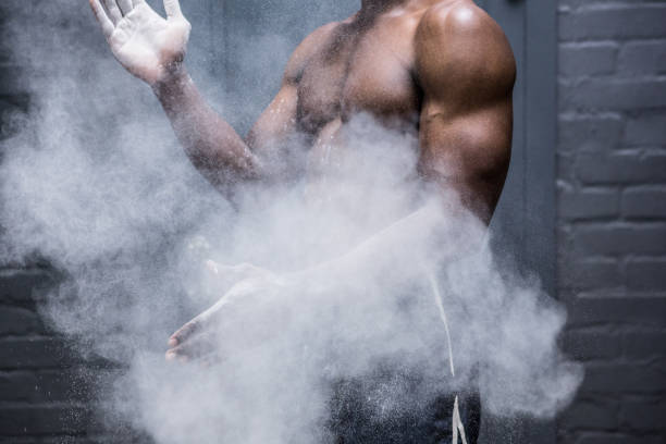 Young Bodybuilder shaking Chalk off his hands stock photo