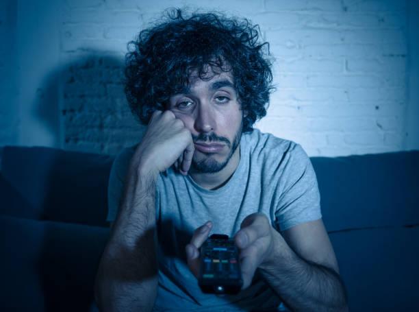 Junge gelangweilte Mann auf der Couch mit TV-Fernbedienung zapping für einen anderen Film oder zeigen spät in der Nacht. Eut uneigennützig und schlaflos. In der Unterhaltung Menschen Schlaflosigkeit und sitzende Lifestyle-Konzept. – Foto