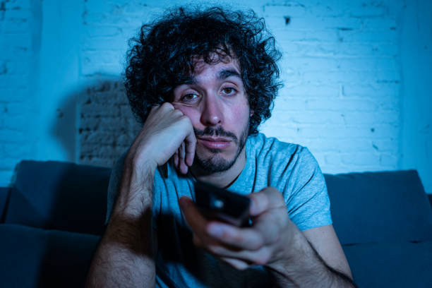 young bored man on couch using tv remote control zapping for another movie or show late at night. looking disinterested and sleepless. in entertainment people insomnia and sedentary lifestyle concept. - noia foto e immagini stock