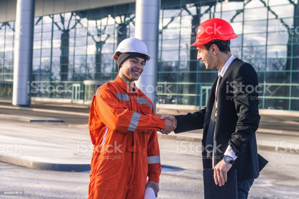 young boss and worker in conversation shaking hands. They wear safety...