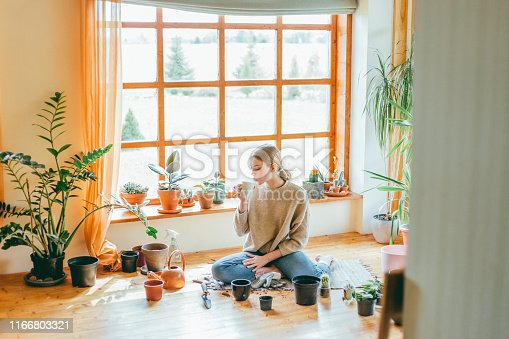Young woman sitting on the floor, taking a coffee break from planting.