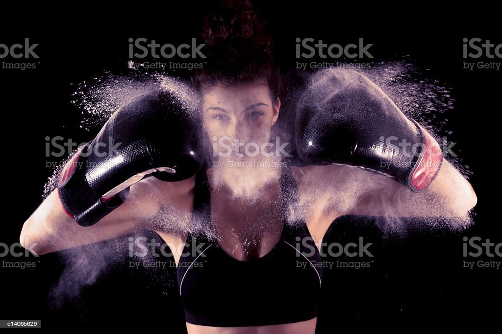 young boxer girl strikes up his gloves in the powder stock photo