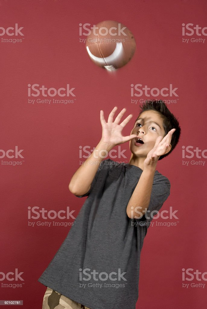Young Boy about to catch a football in the studio royalty-free stock photo