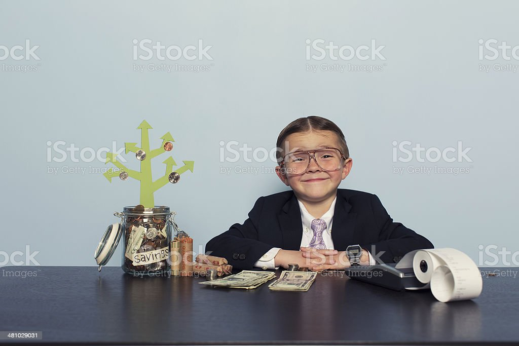 Young Boy Accountant Grows Money in Savings Account stock photo